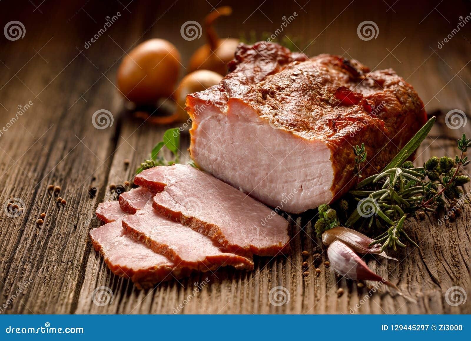 Carni affumicate, lonza di maiale affumicata affettata su una tavola di legno con l aggiunta delle erbe fresche e spezie aromatic
