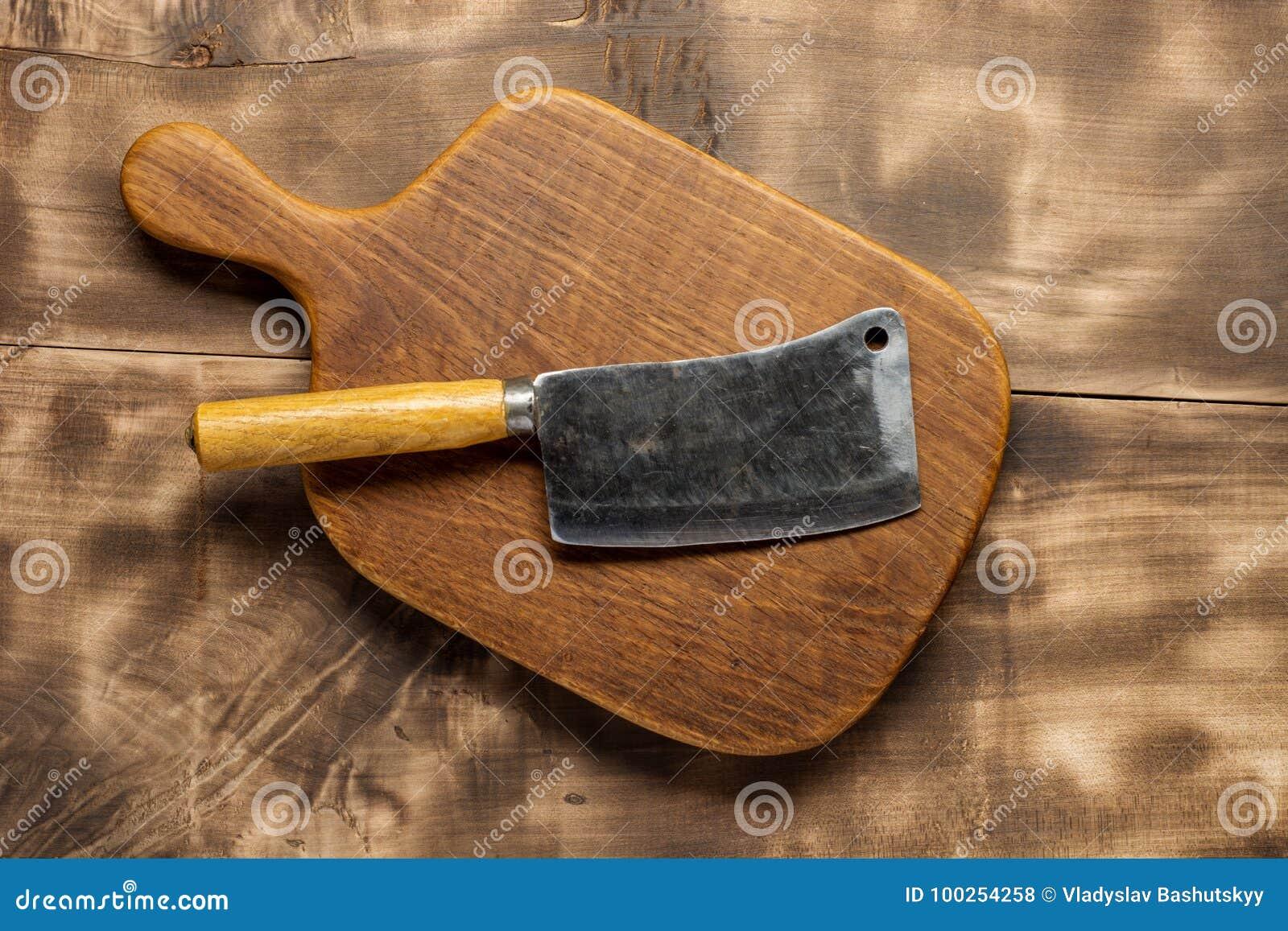 Carnicero Cuchillas de la carne de matadero del vintage con la tajadera en fondo de madera oscuro