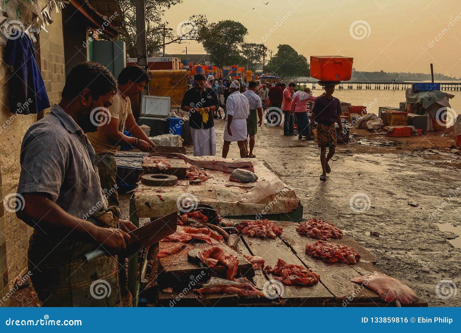 Carnicero que corta la carne en un mercado de pescados en Thalassery, Kerala la India