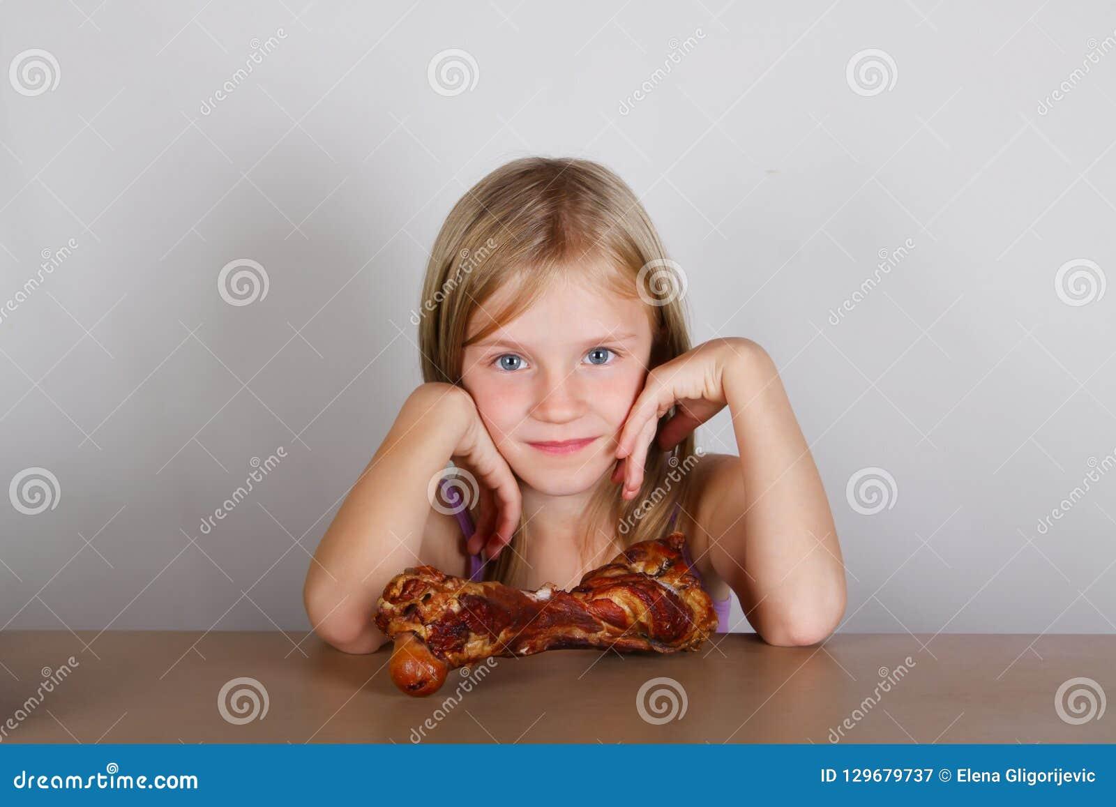 Carnivore keto diety pojęcie - mała blond dziewczyna je surowego mięso