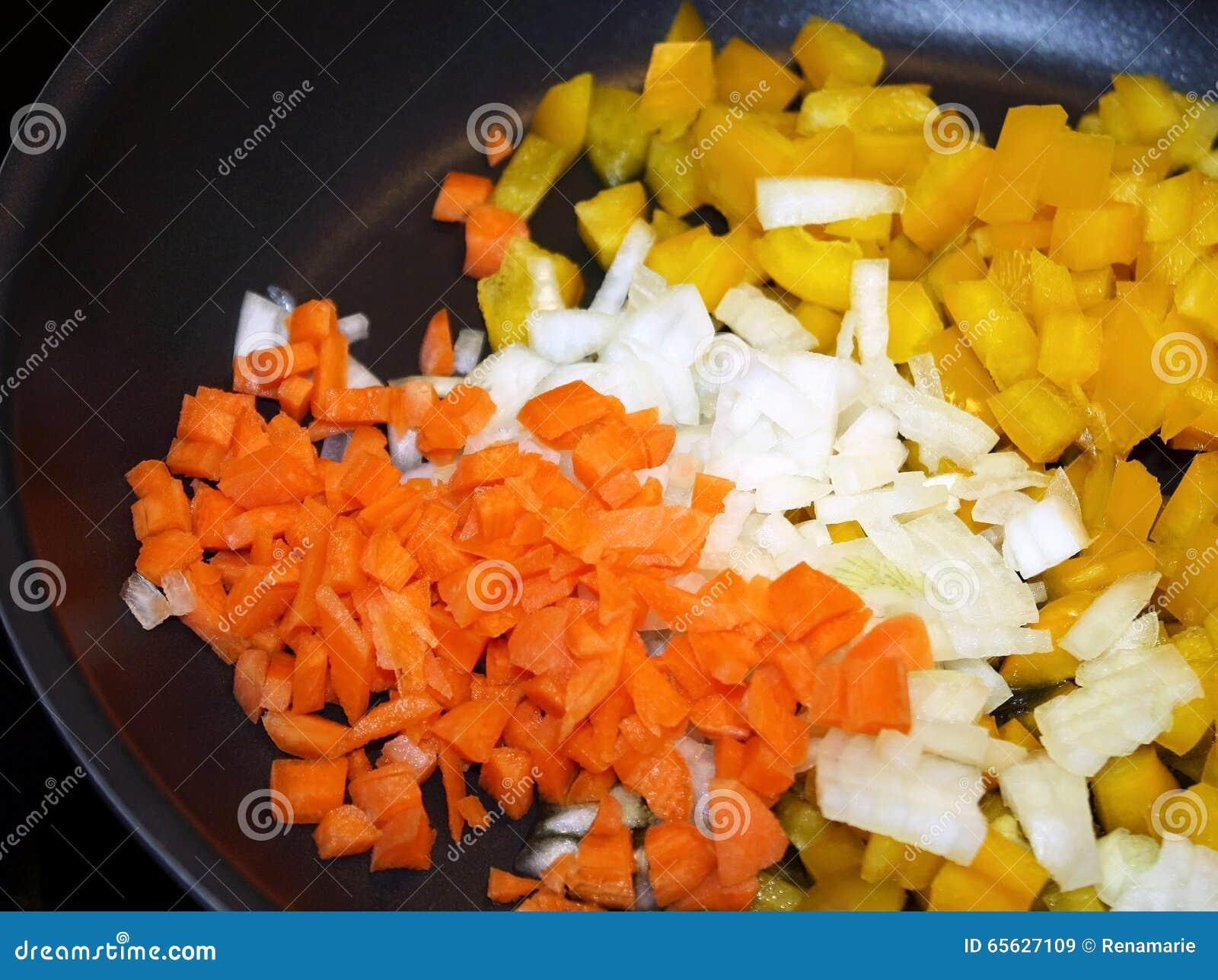 Carottes crues découpées, oignons et poivrons jaunes dans la poêle