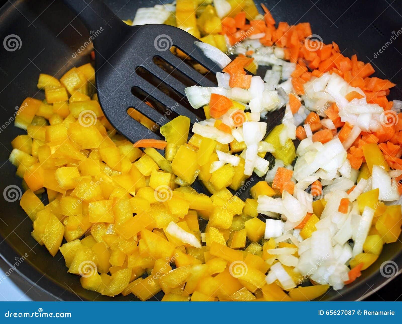 Carottes crues découpées, oignons et poivrons jaunes dans la poêle prête pour le sauté
