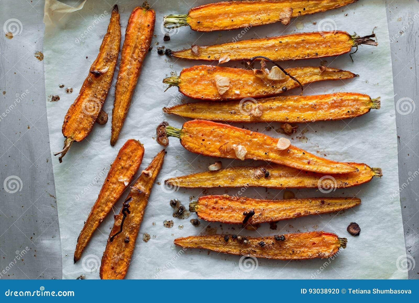 Carottes rôties de ressort sur le parchemin avec l ail, les pois de poivre et la coriandre