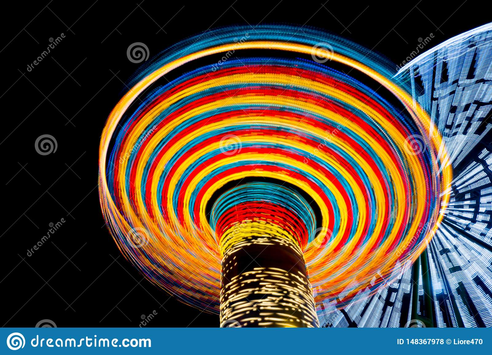 Carousel и ferris катят внутри парк атракционов вечером, долгая выдержка Концепция скорости