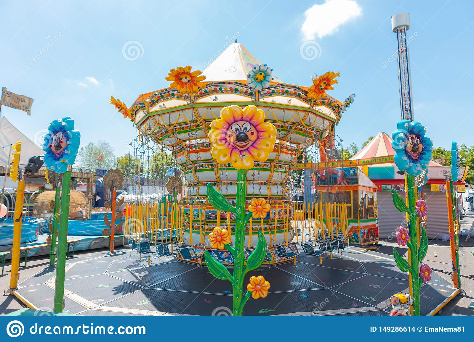 Carousel chains for children in bright colors during a fair in an Italian park flower shaped lights