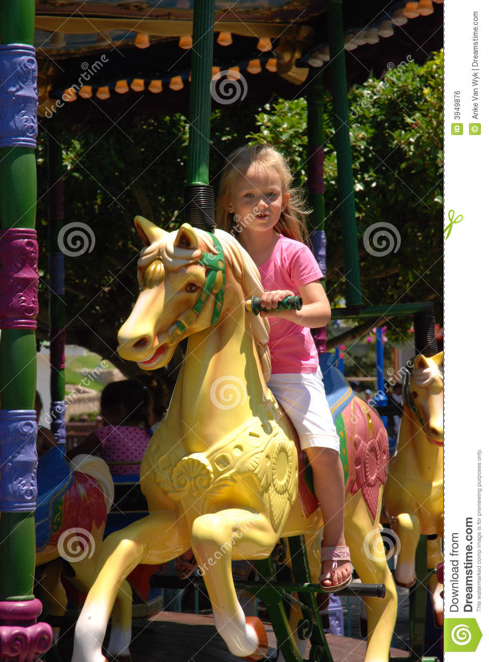 ... facial expression riding on a horse on a merry-go-round outdoors