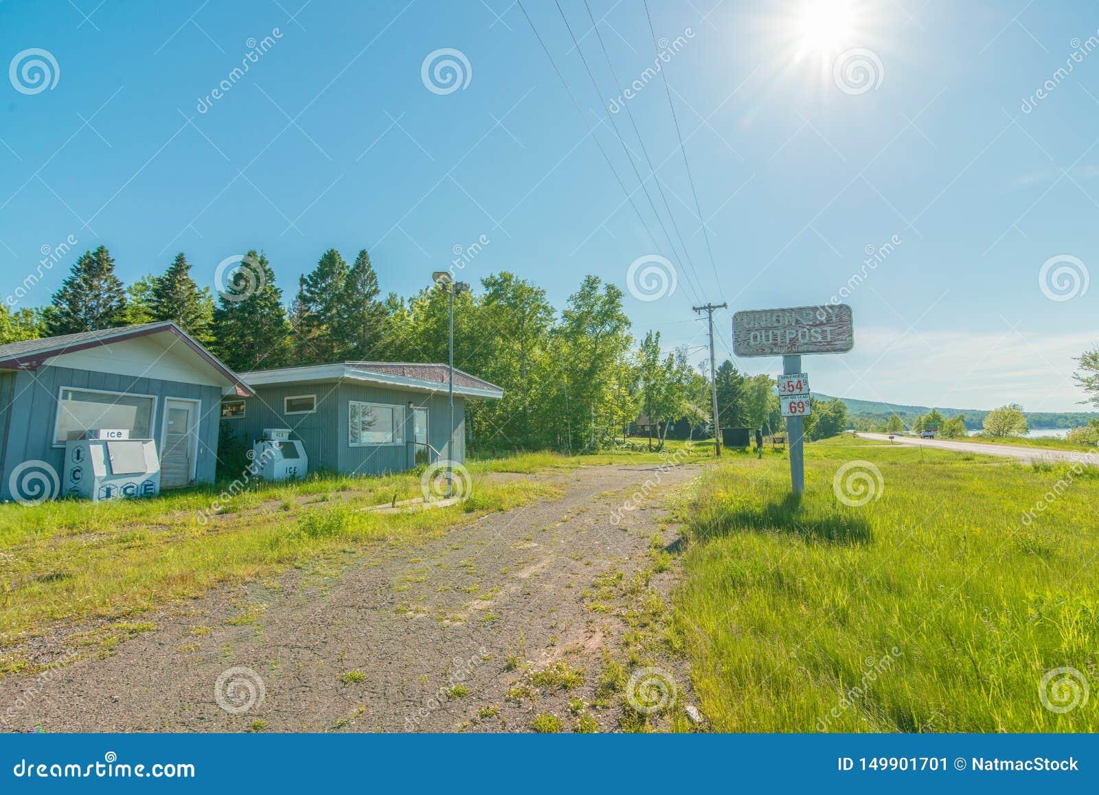 CARP LAKE TOWNSHIP, MICHIGAN / USA - JUNE 16, 2016: Abandoned shut down gas station / convenience store - nature growing back - ru