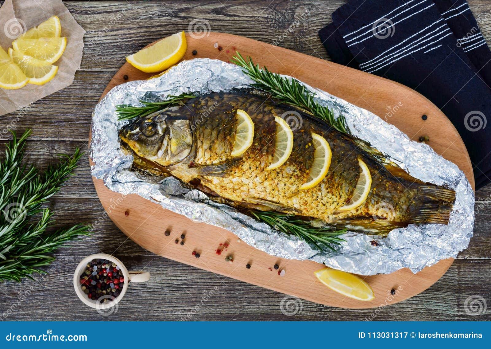 Carpa cocida grande con las hierbas, el limón y las especias en hoja en un fondo de madera