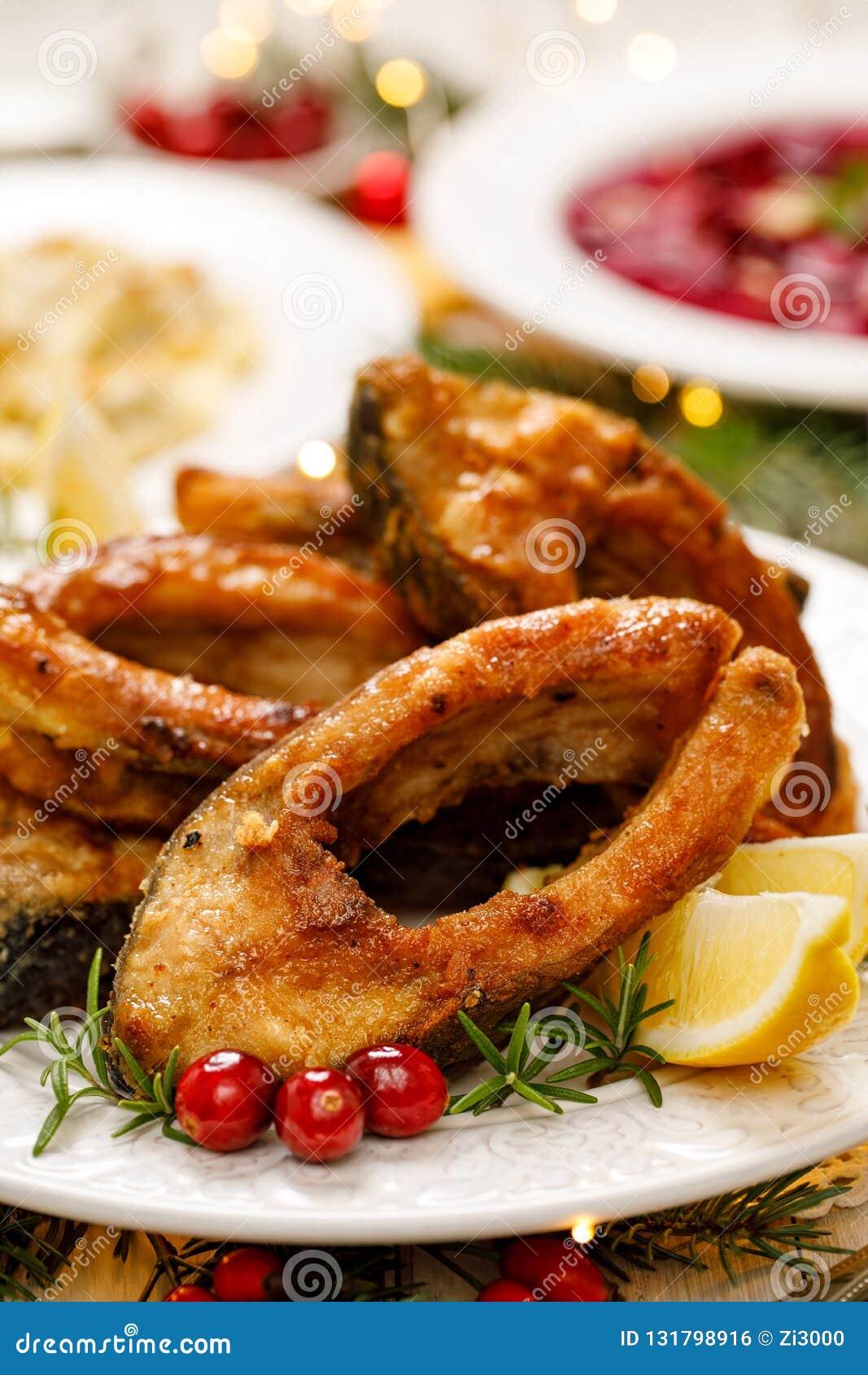 Carpa do Natal, fatias de peixes fritadas em uma placa branca, fim da carpa acima