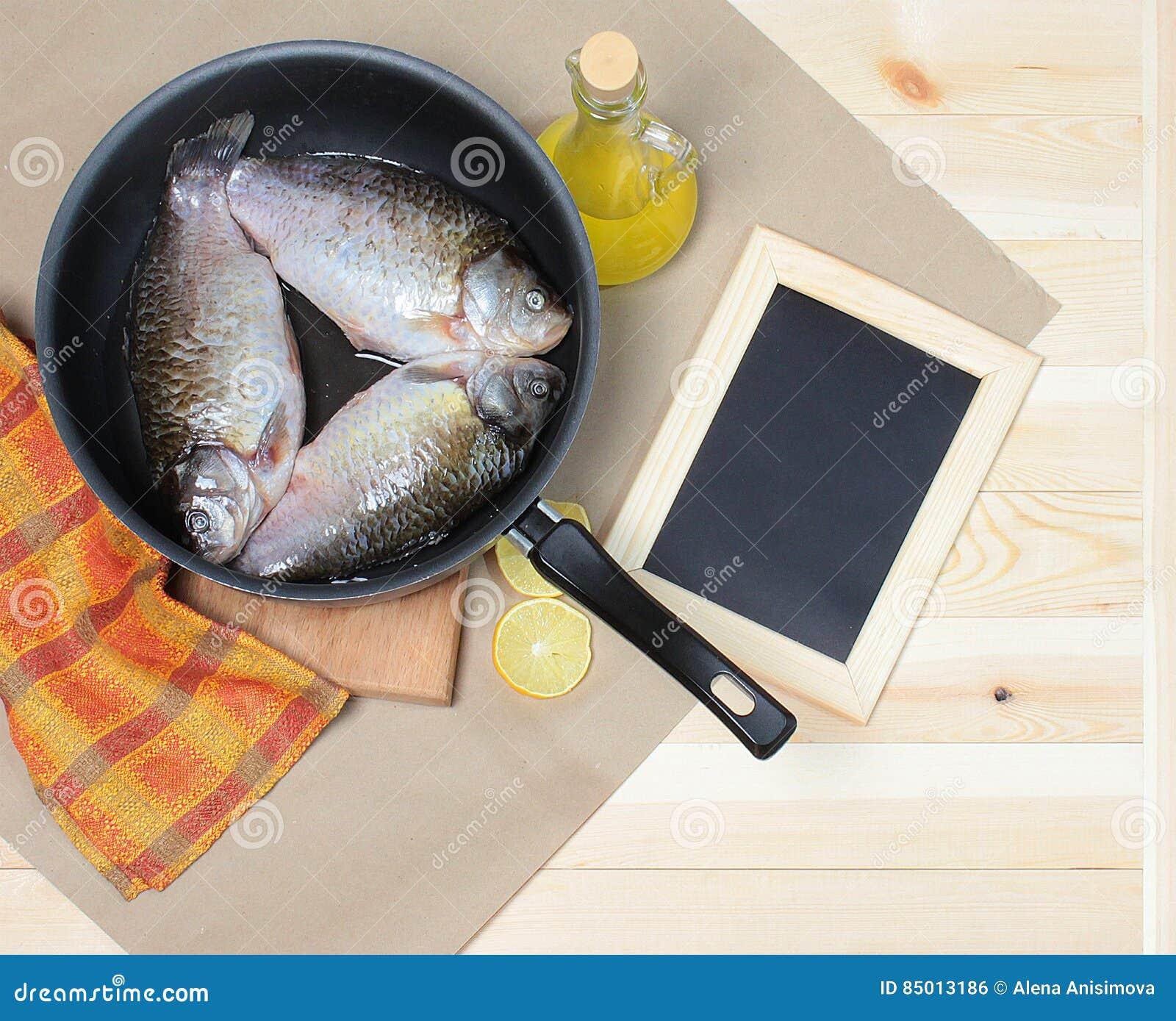 Carpa en el sartén con el aceite vegetal y el limón en el papel de Kraft, al lado de la pizarra