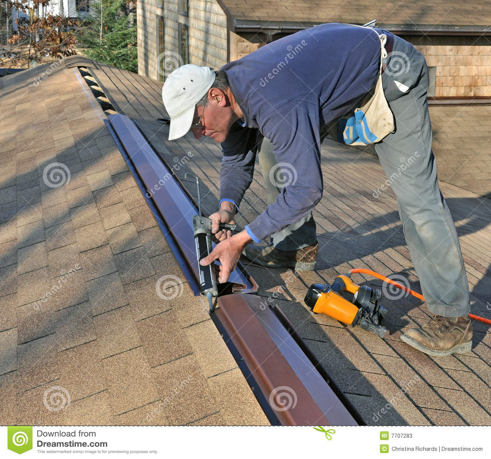 Carpenter Applying Caulk To Ridge Vent Stock Image Image