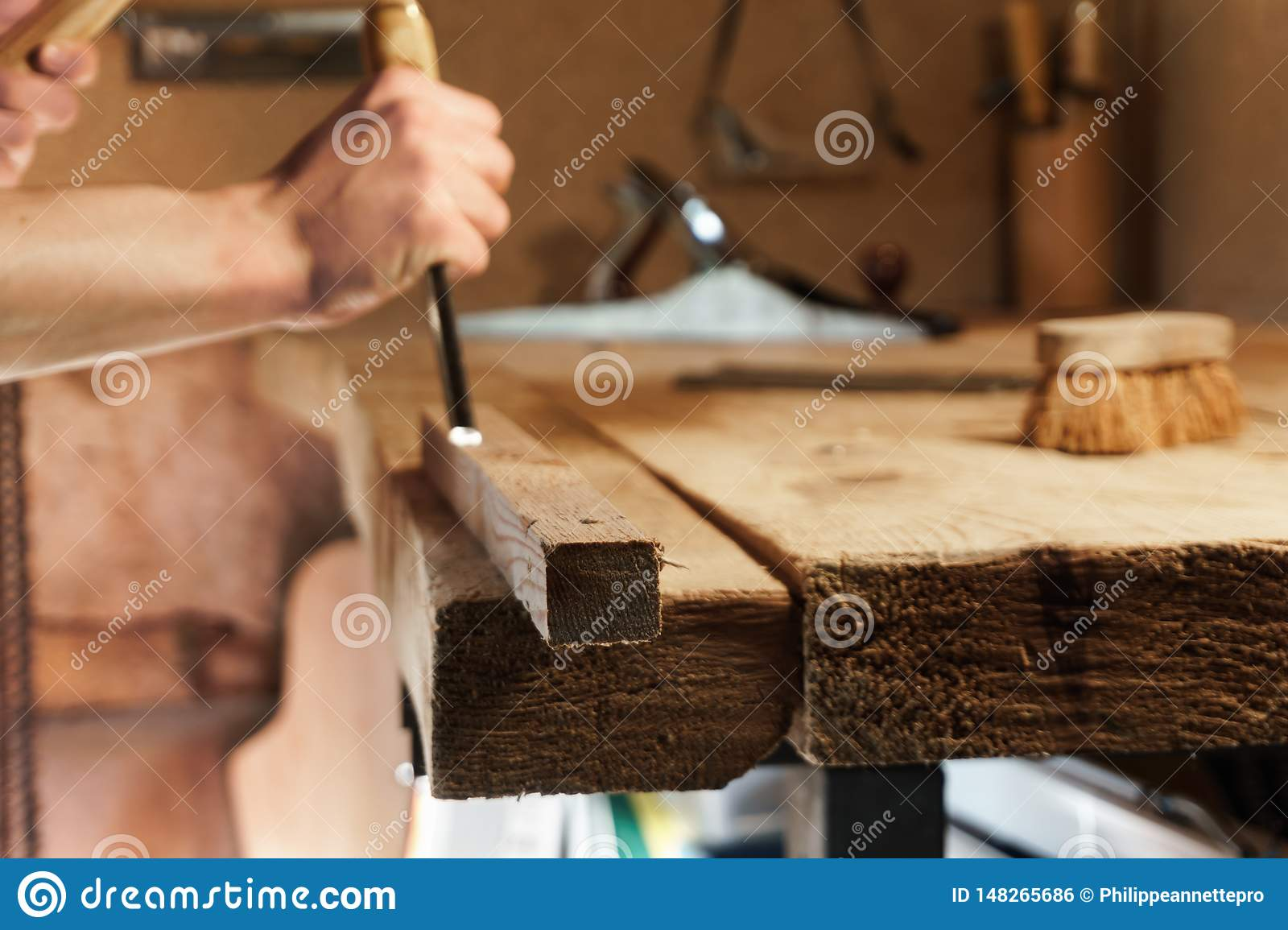 Carpenter carving wood with a chisel
