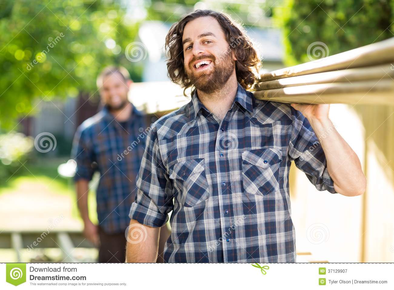 Carpenter With Coworker Carrying Planks While