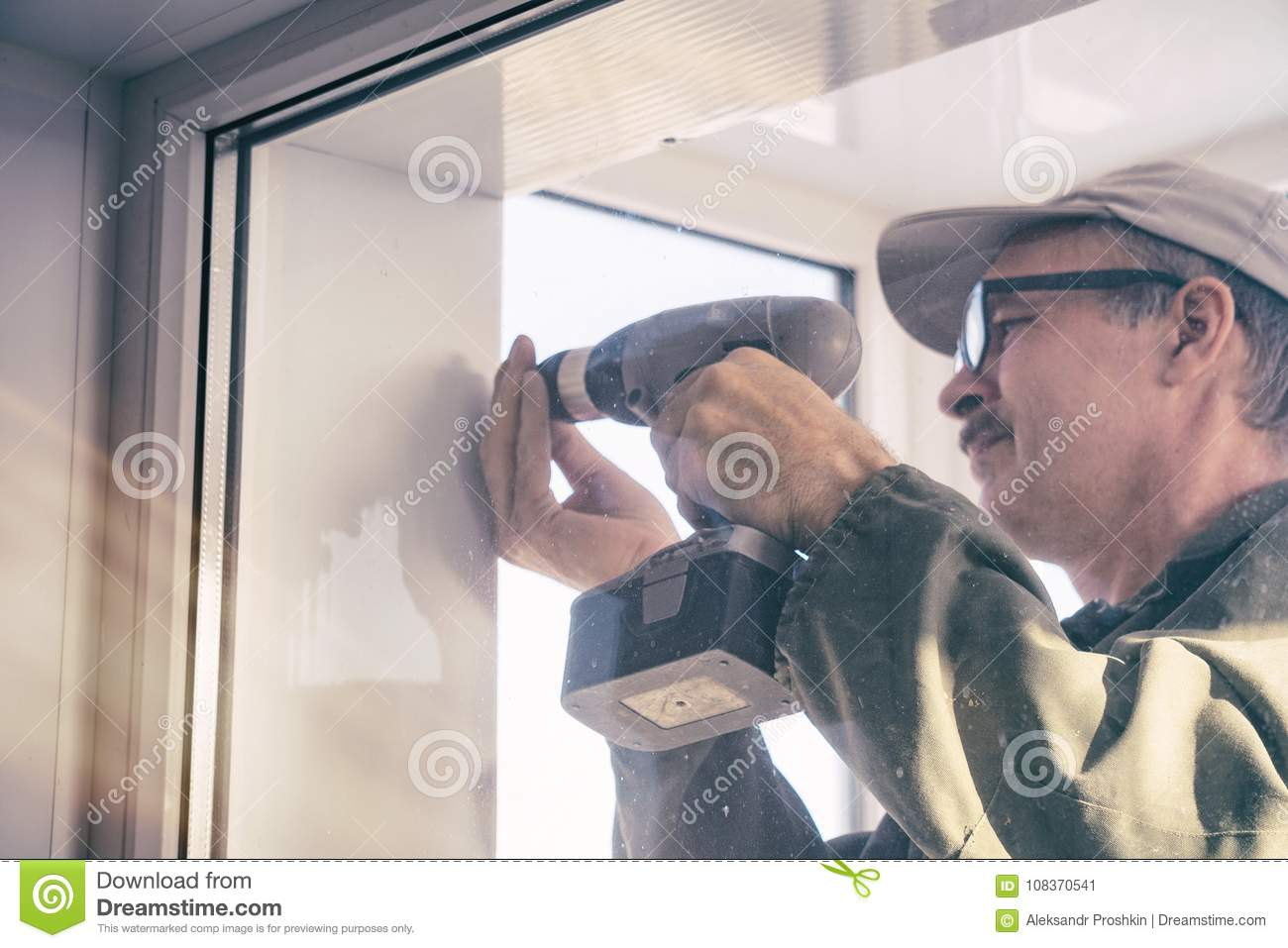 Carpenter in glasses with a drill