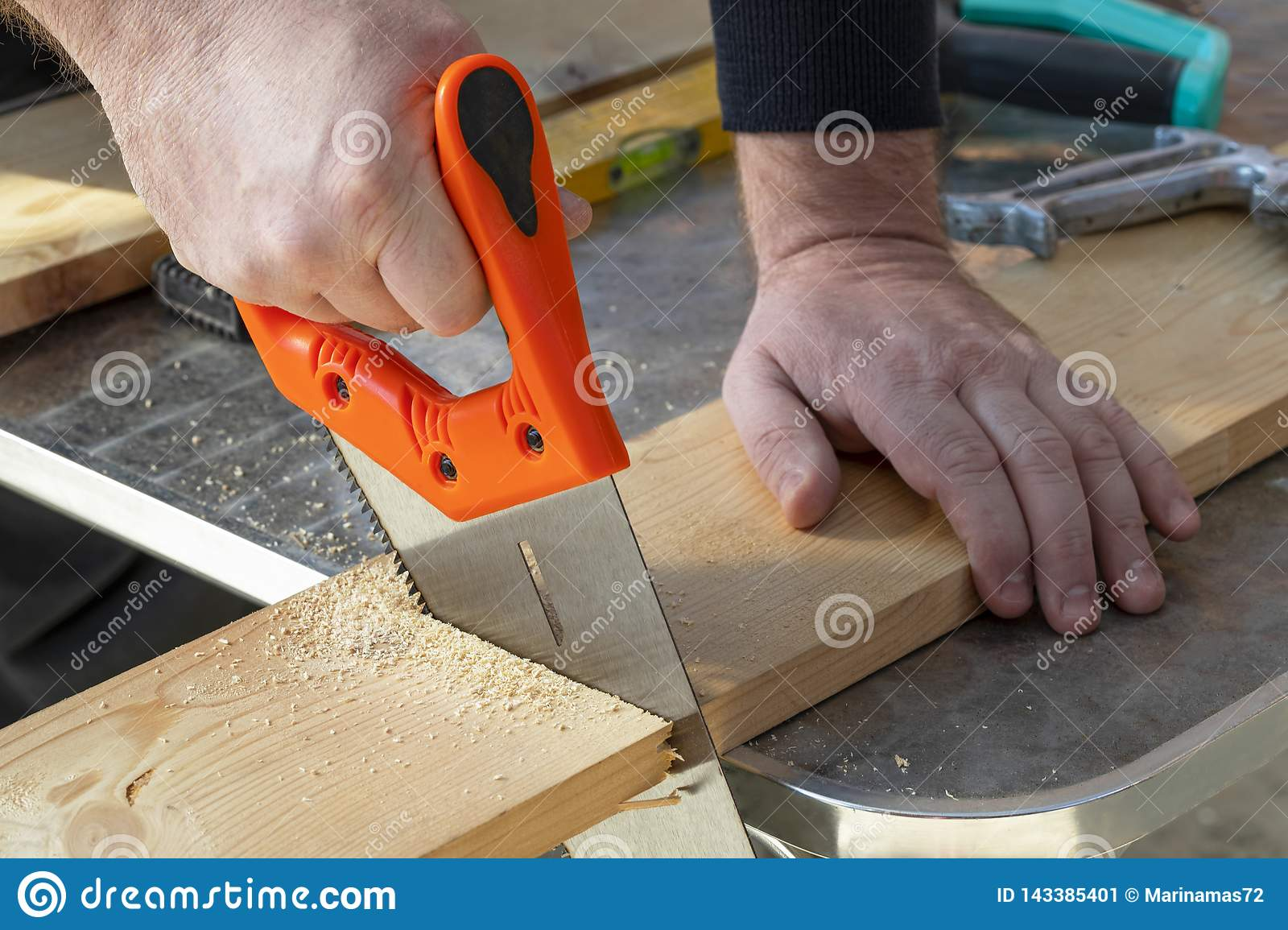 Carpenter Hand With Handsaw Cutting Wooden Boards  Stock
