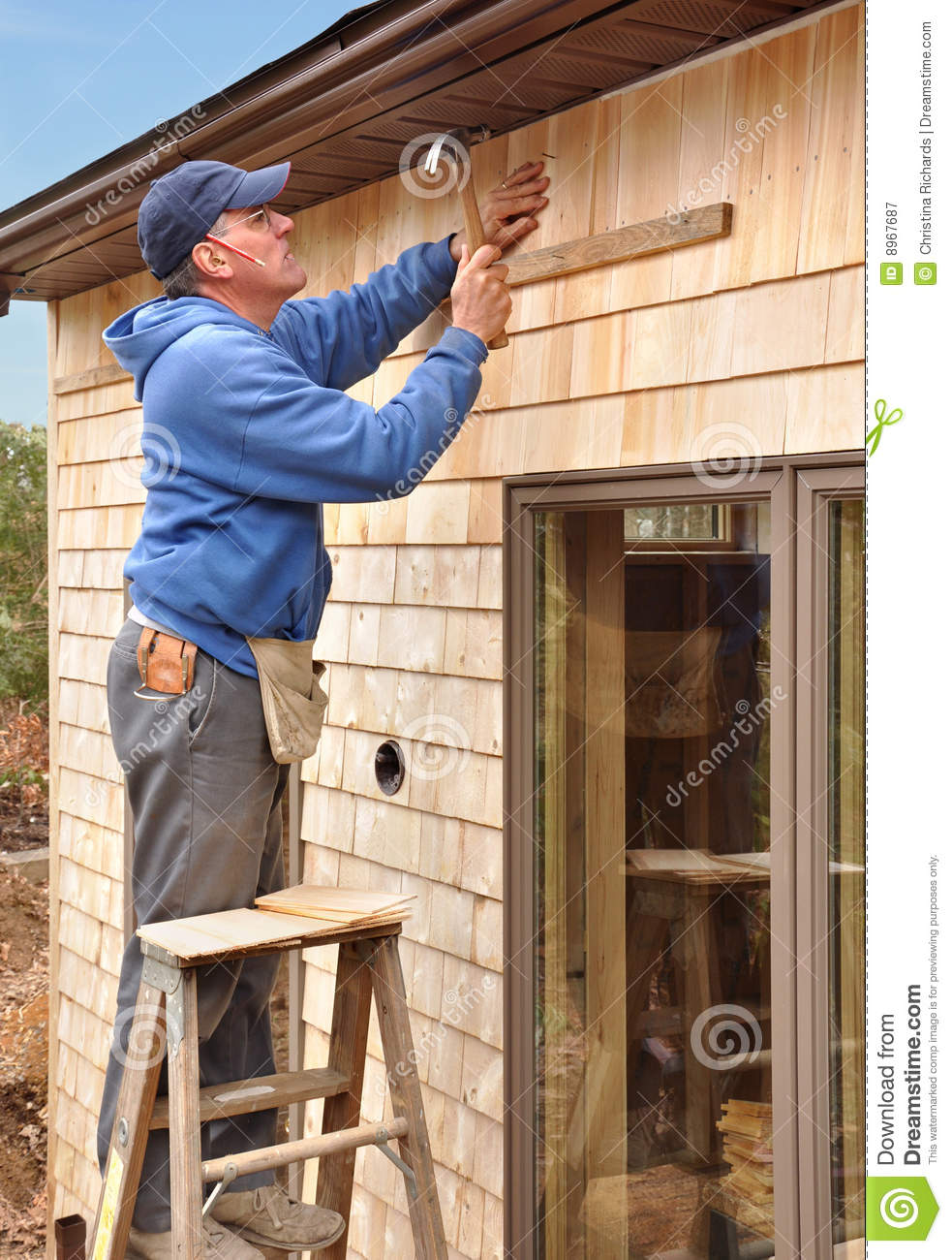 carpenter installing cedar shingles 8967687