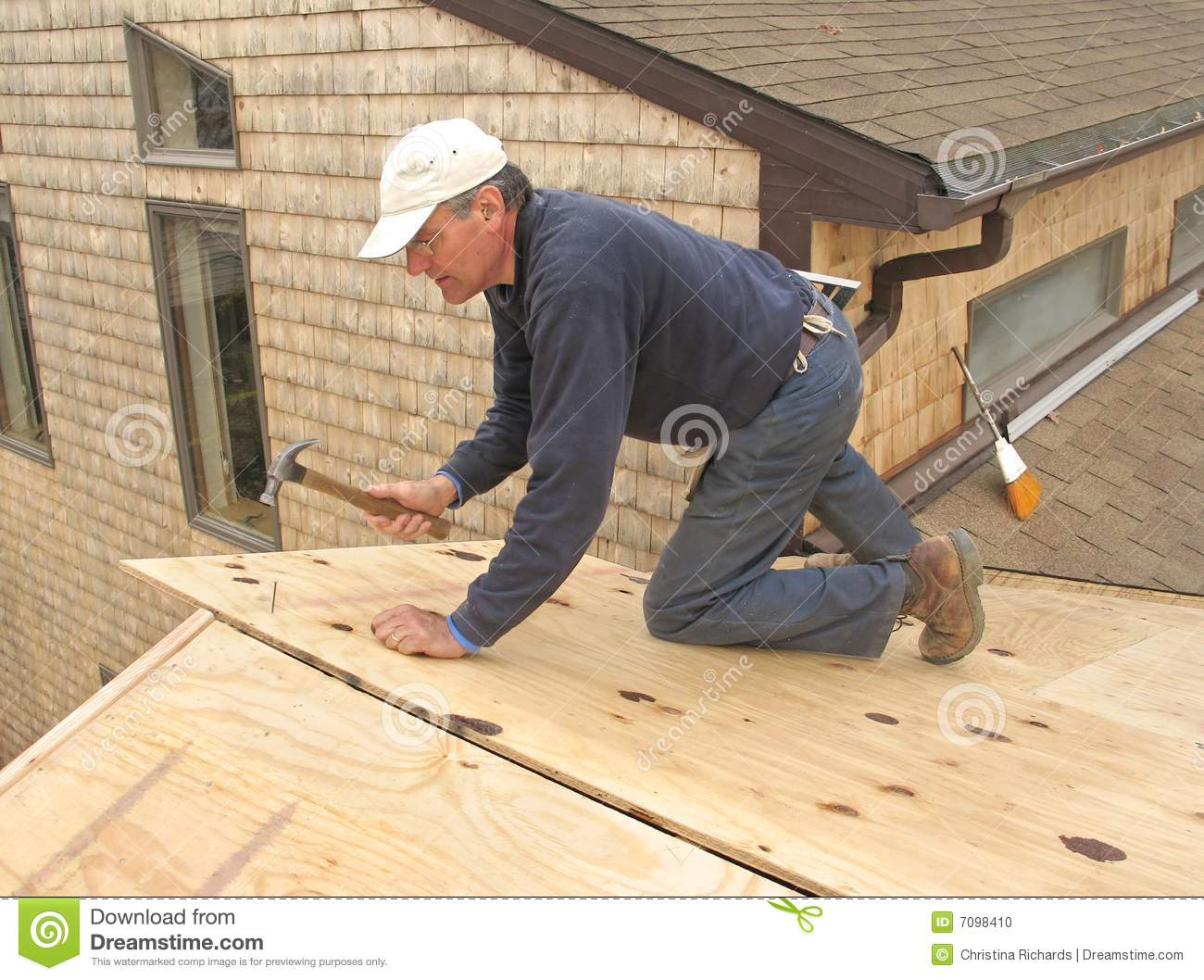 Carpenter installing sheathing to roof stock photo image for Roof sheathing material