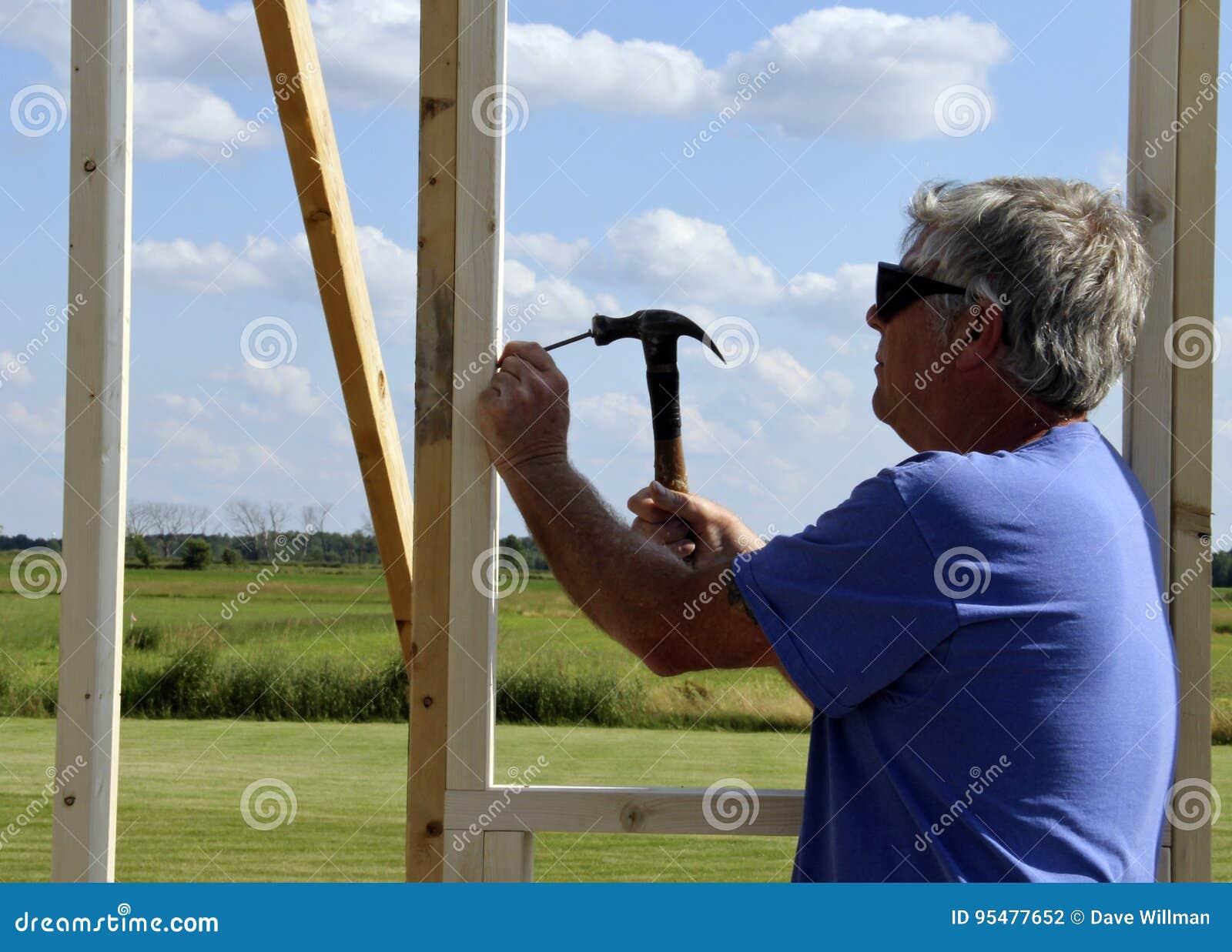 Carpenter nailing with a hammer