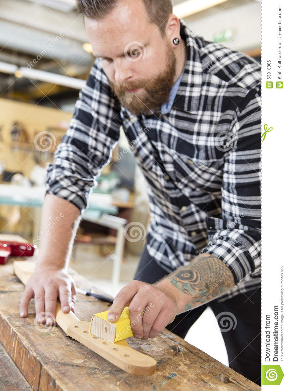 Carpenter sanding a guitar neck in wood at workshop stock for Working man tattoo