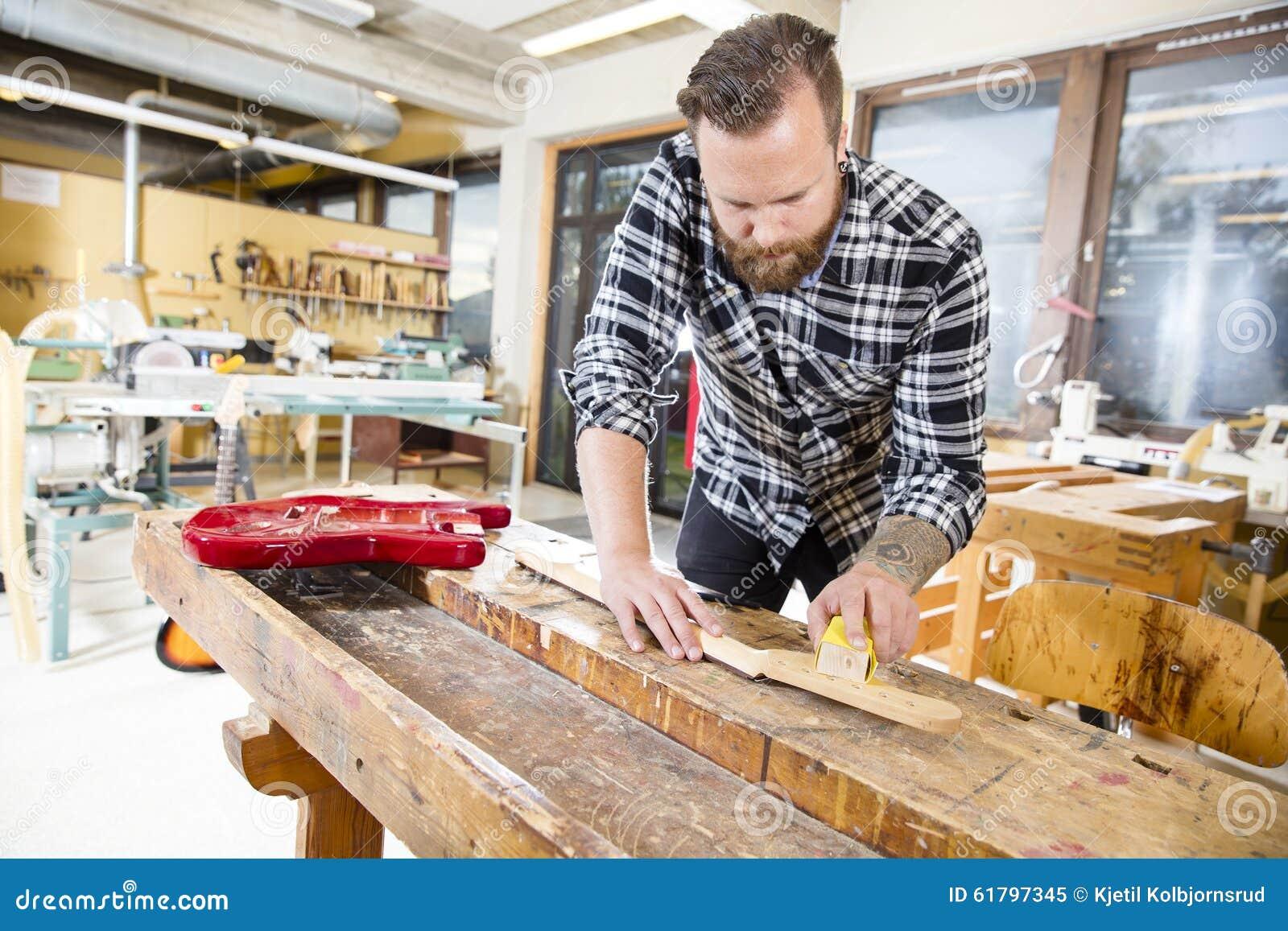 Carpenter sanding a wooden guitar neck in workshop stock for Working man tattoo