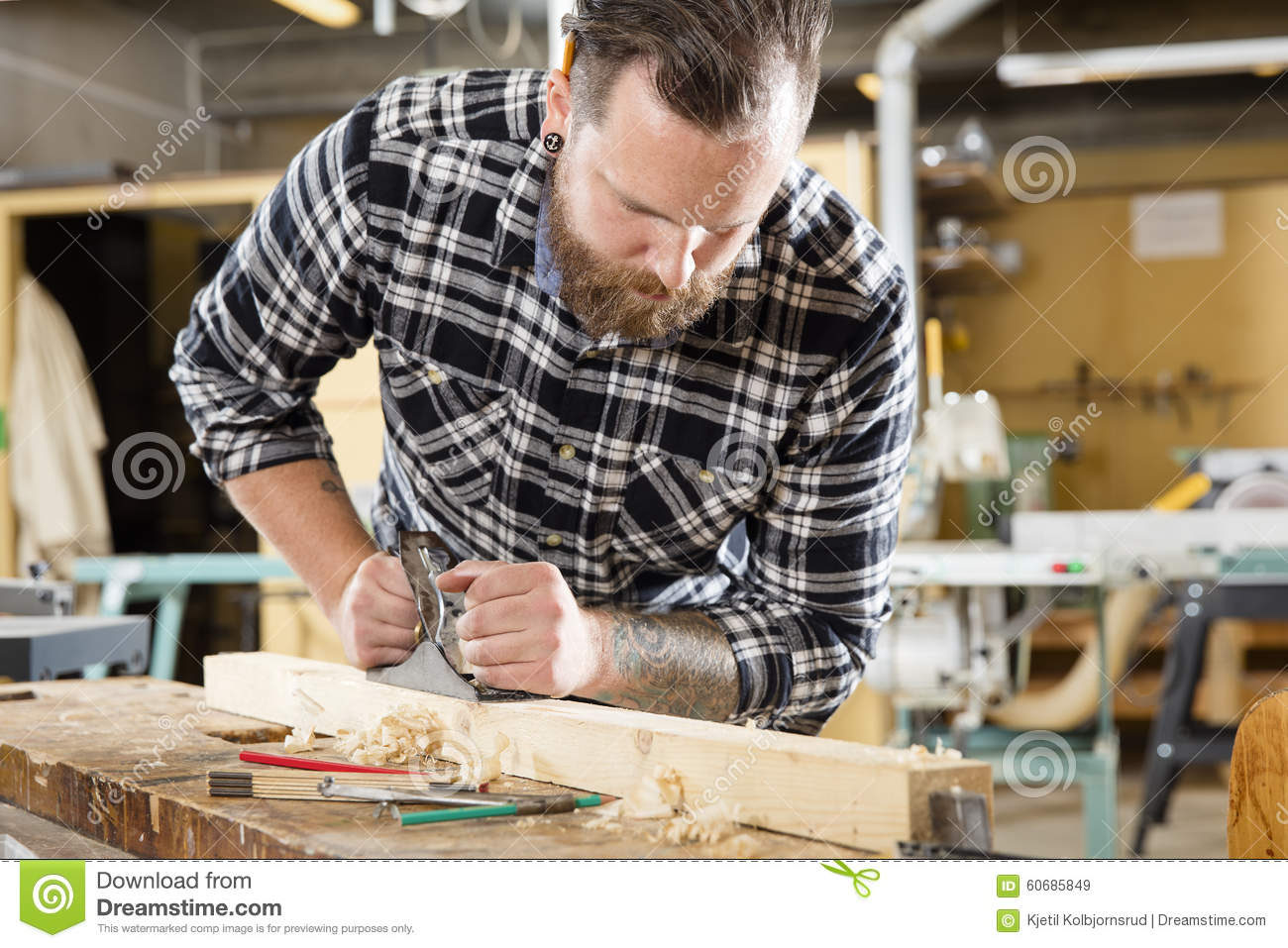 Carpenter work with plane on wood plank in workshop stock for Working man tattoo
