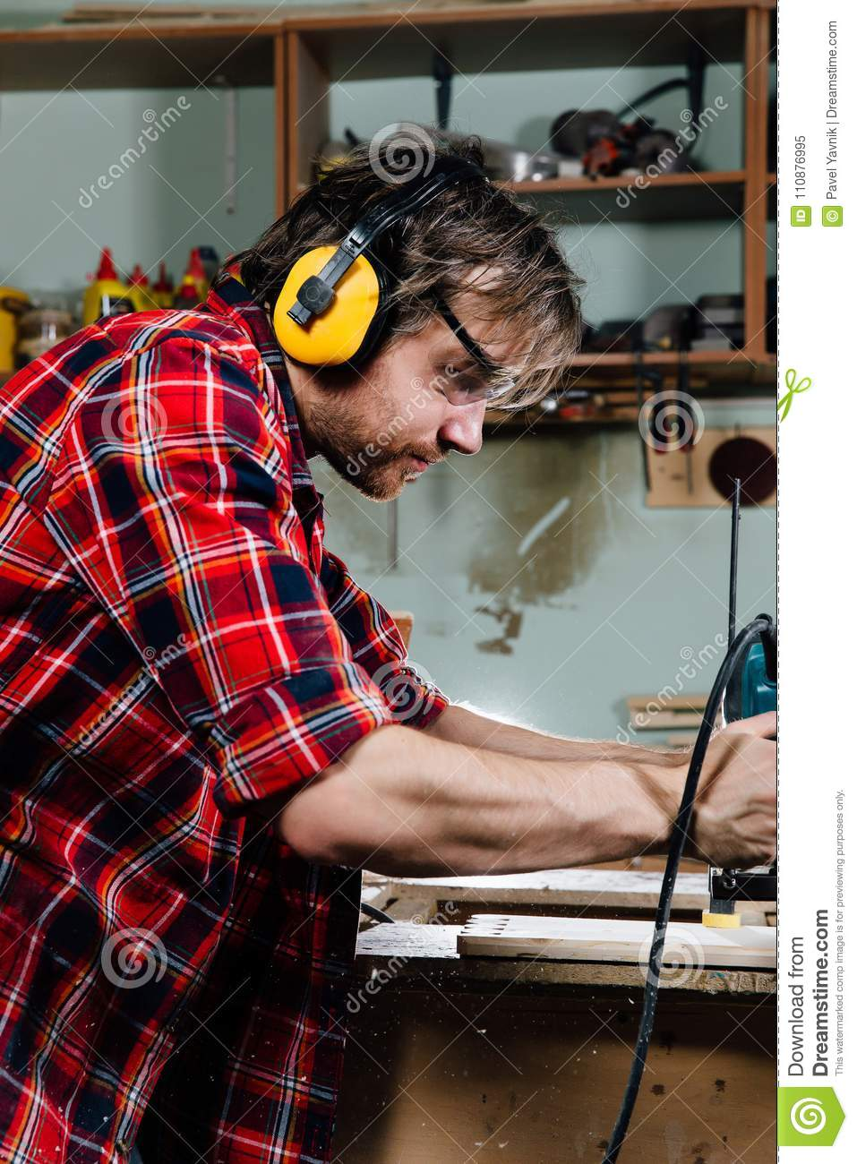 Carpenter working of manual hand milling machine in the carpentry workshop. joiner.