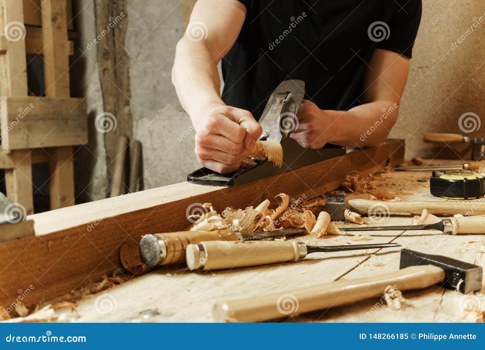 Carpentiere che lavora un bordo di legno con un aereo