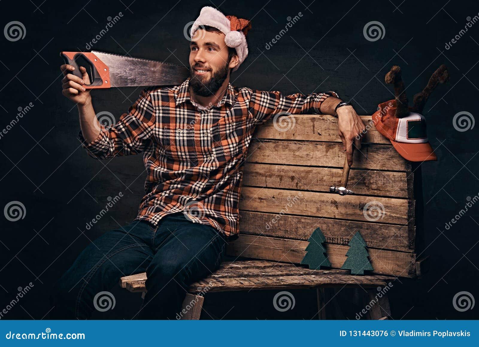 Carpentiere che porta il cappello decorato di Santa che si siede su una tavolozza di legno