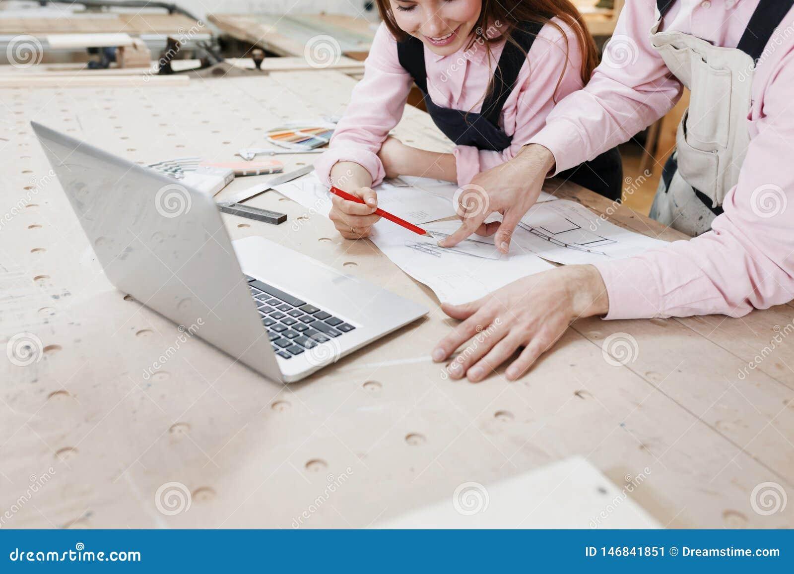 Carpentiere della donna di affari che lavora al computer portatile su superficie di legno fra gli strumenti della costruzione Vic