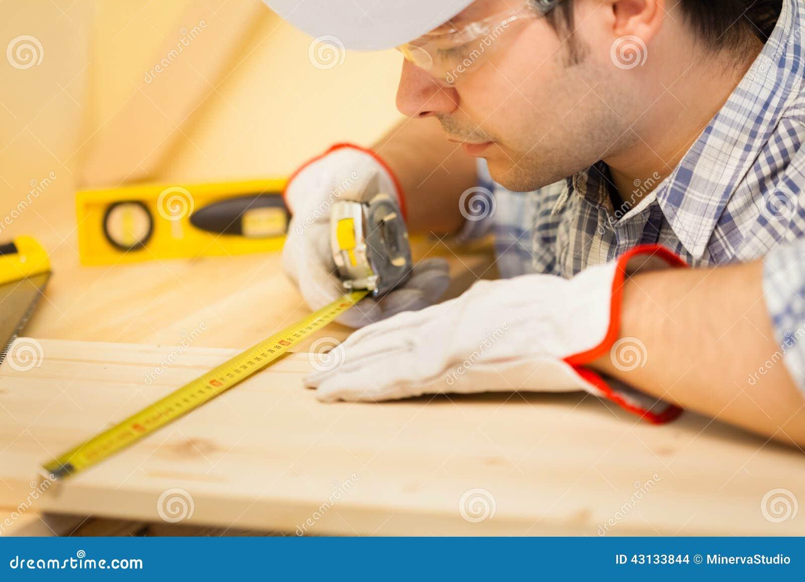 Carpentiere sul lavoro facendo uso di un nastro di misurazione