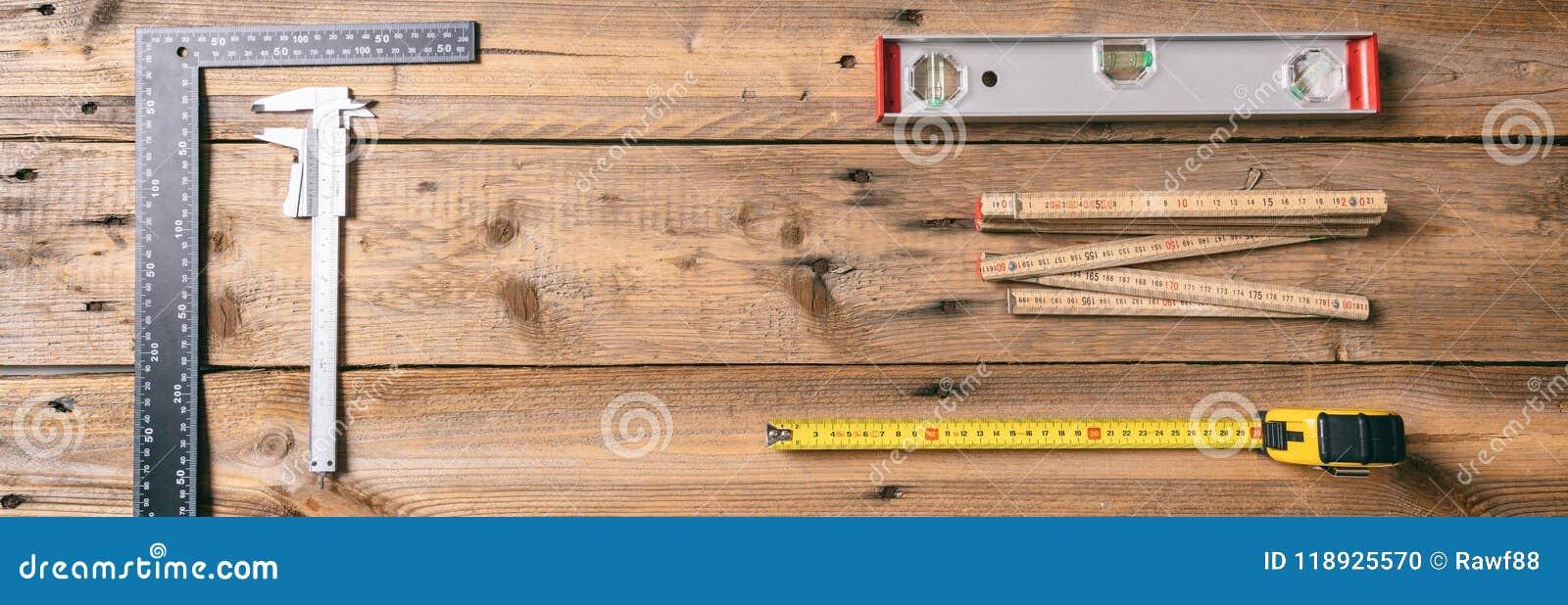 Carpentry Meça a fita, o nível de espírito e as réguas no fundo de madeira, bandeira, espaço da cópia, vista superior