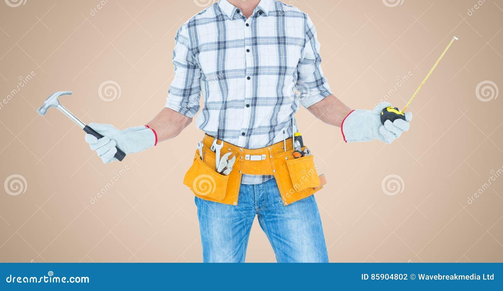 Carpinteiro com martelo e a fita de medição contra o fundo de creme