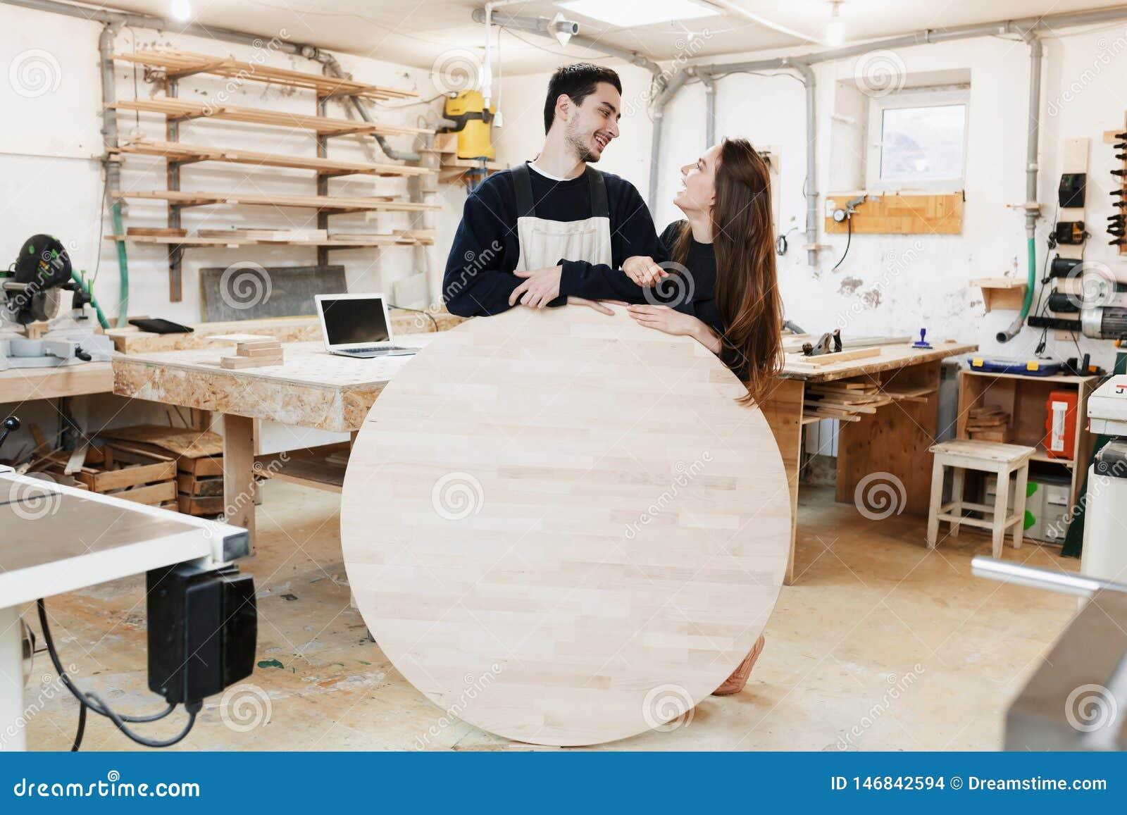 Carpinteiro novo na oficina do carpinteiro O homem guarda uma placa redonda de madeira para o texto Copyspace especialista novo,