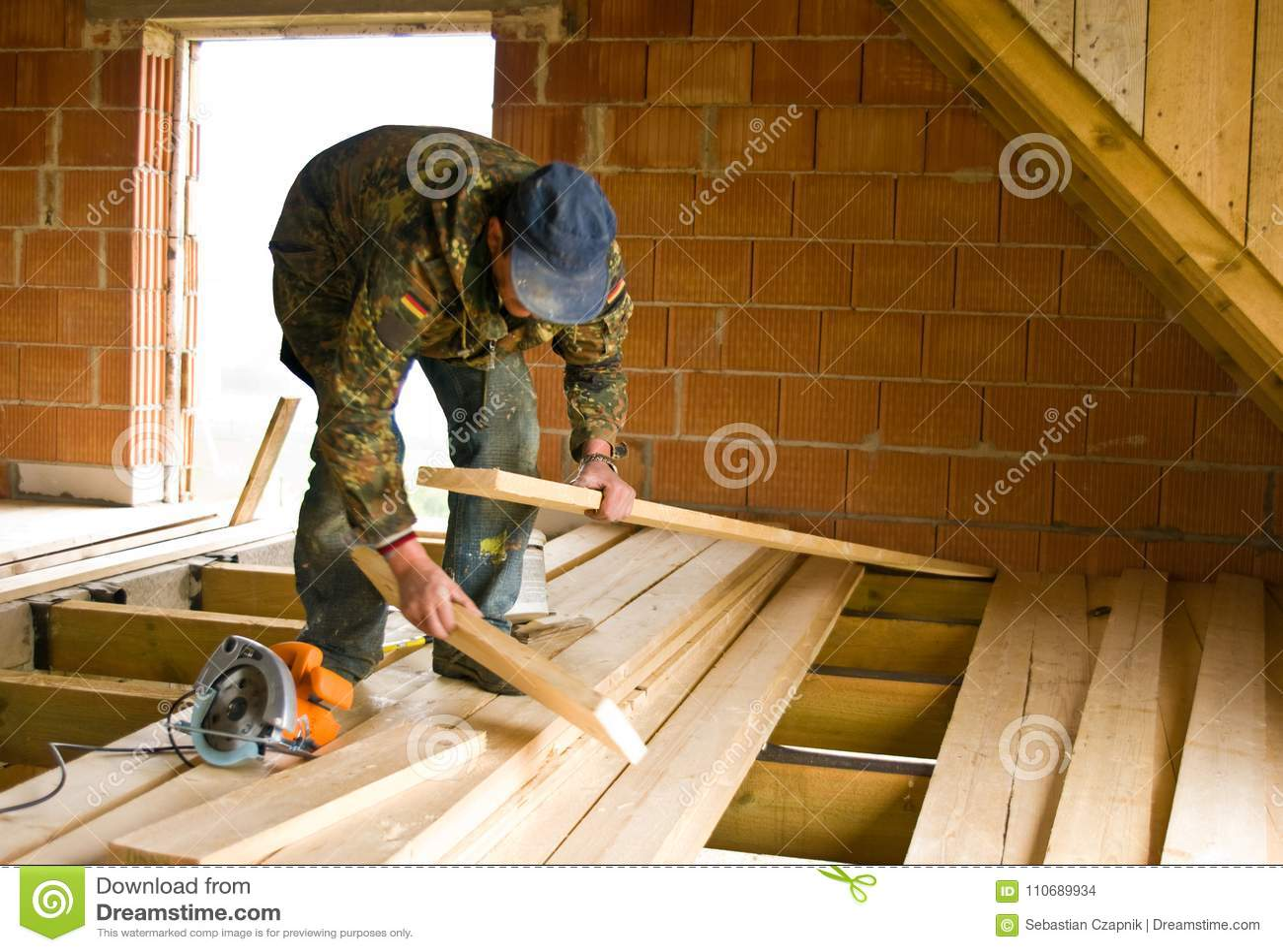 Carpinteiro que constrói o assoalho novo de uma sala do sótão