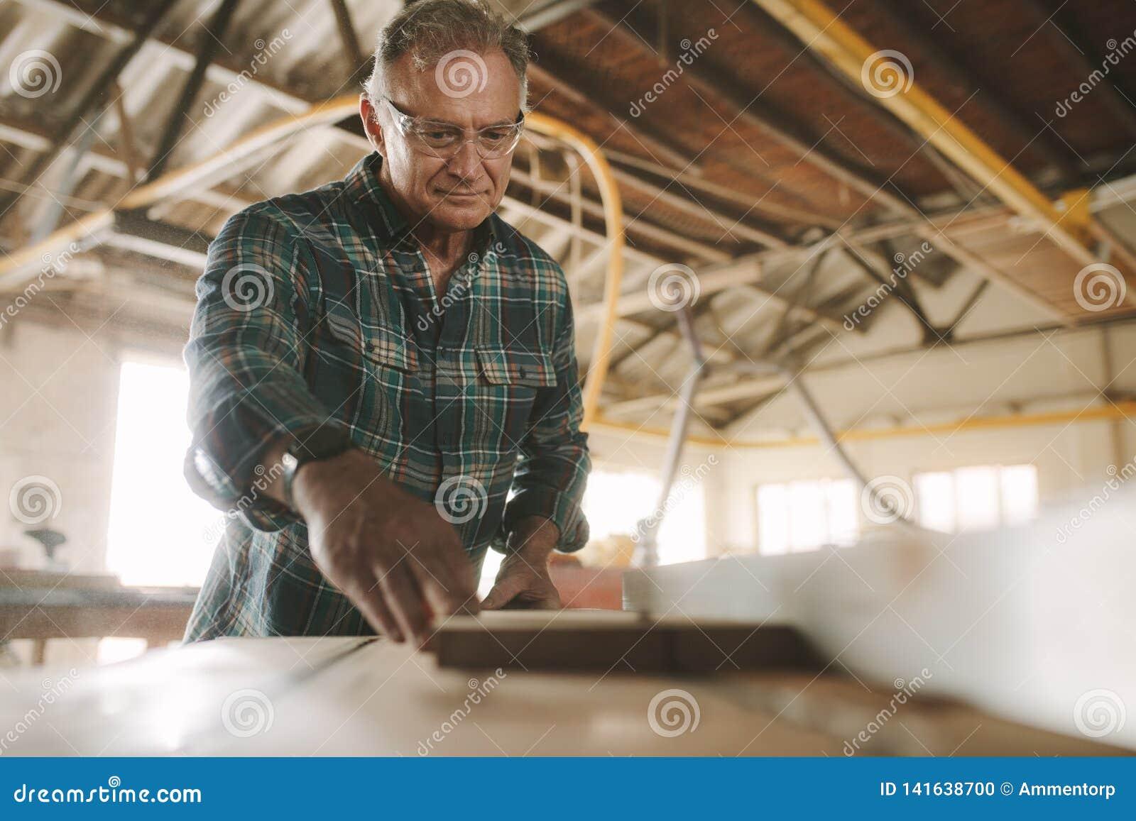 Carpinteiro que corta as pranchas de madeira na serra elétrica