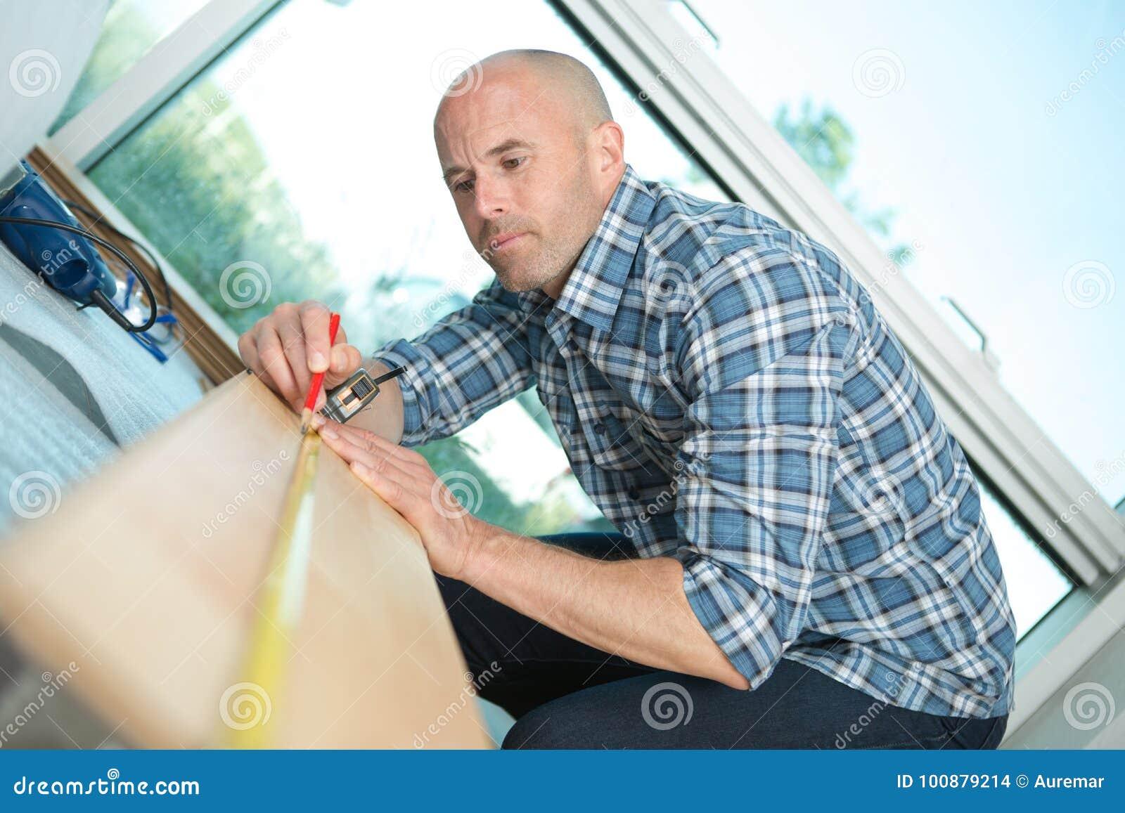 Carpinteiro que trabalha disponível a placa de madeira de medição com régua