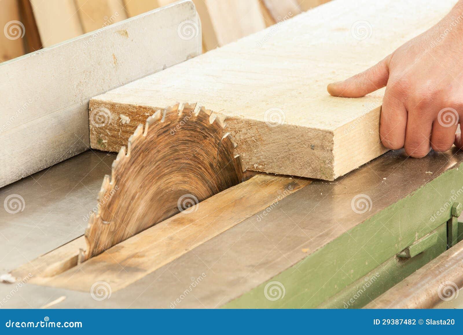Carpinteiro que trabalha em máquinas do woodworking na loja da carpintaria