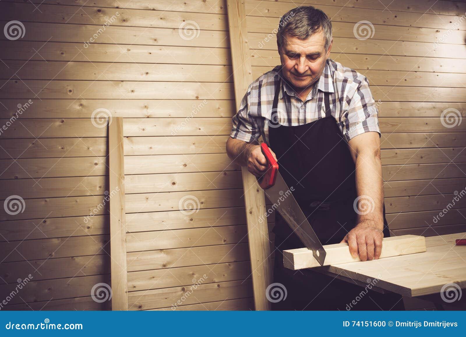 Carpinteiro superior que trabalha em sua oficina