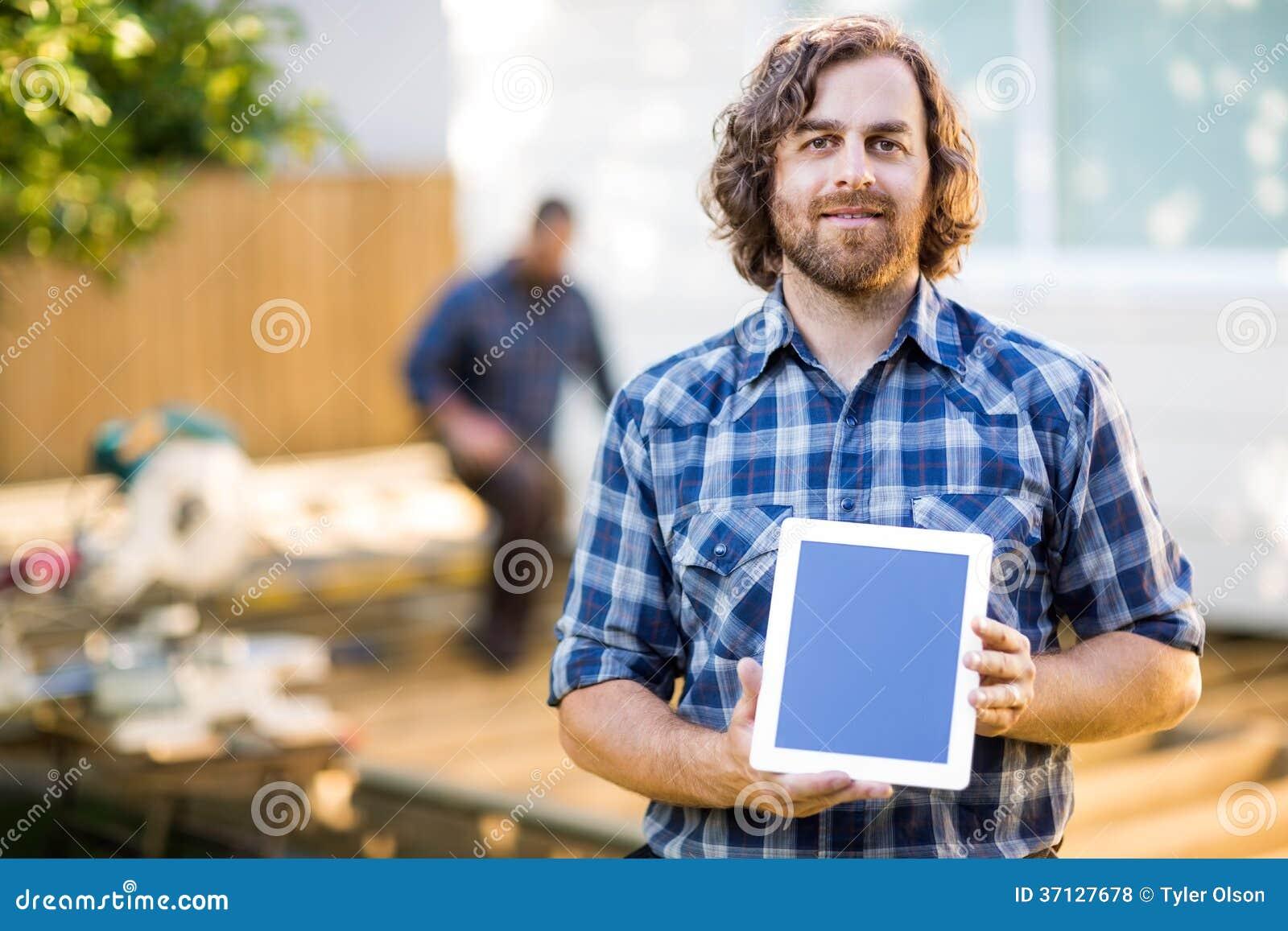 Carpintero Displaying Tablet Computer con el compañero de trabajo