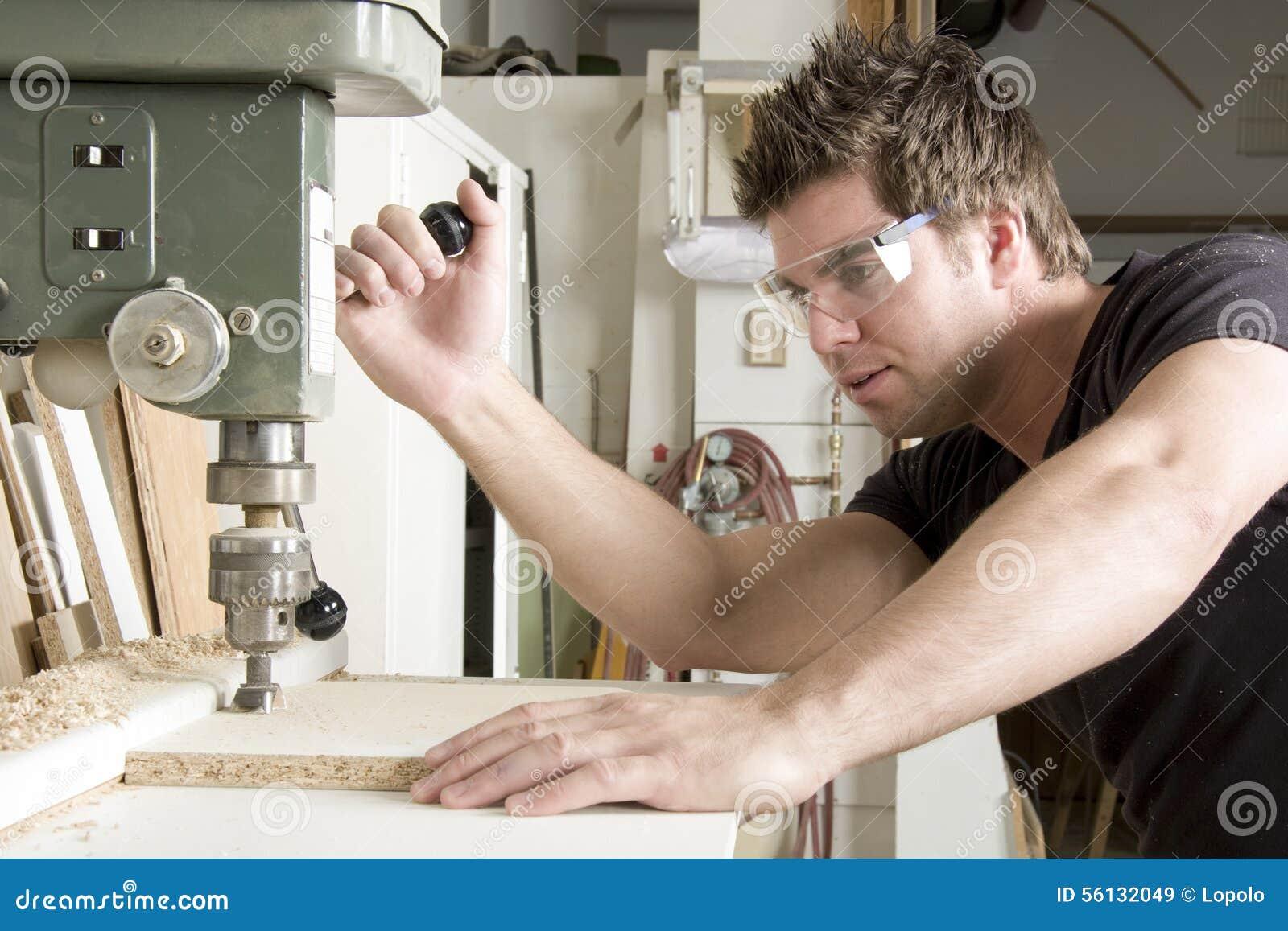 Carpintero en el trabajo sobre trabajo usando la herramienta eléctrica