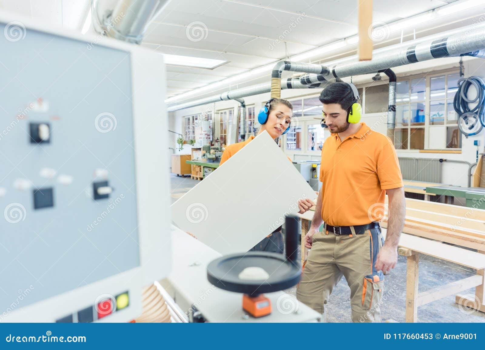 Carpintero en la fábrica de los muebles que examina el pedazo en el QA