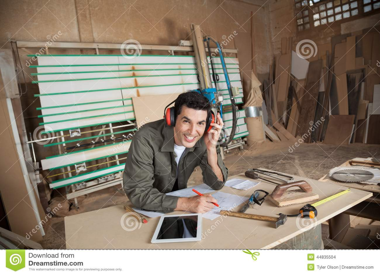 Carpintero feliz Working On Blueprint en taller