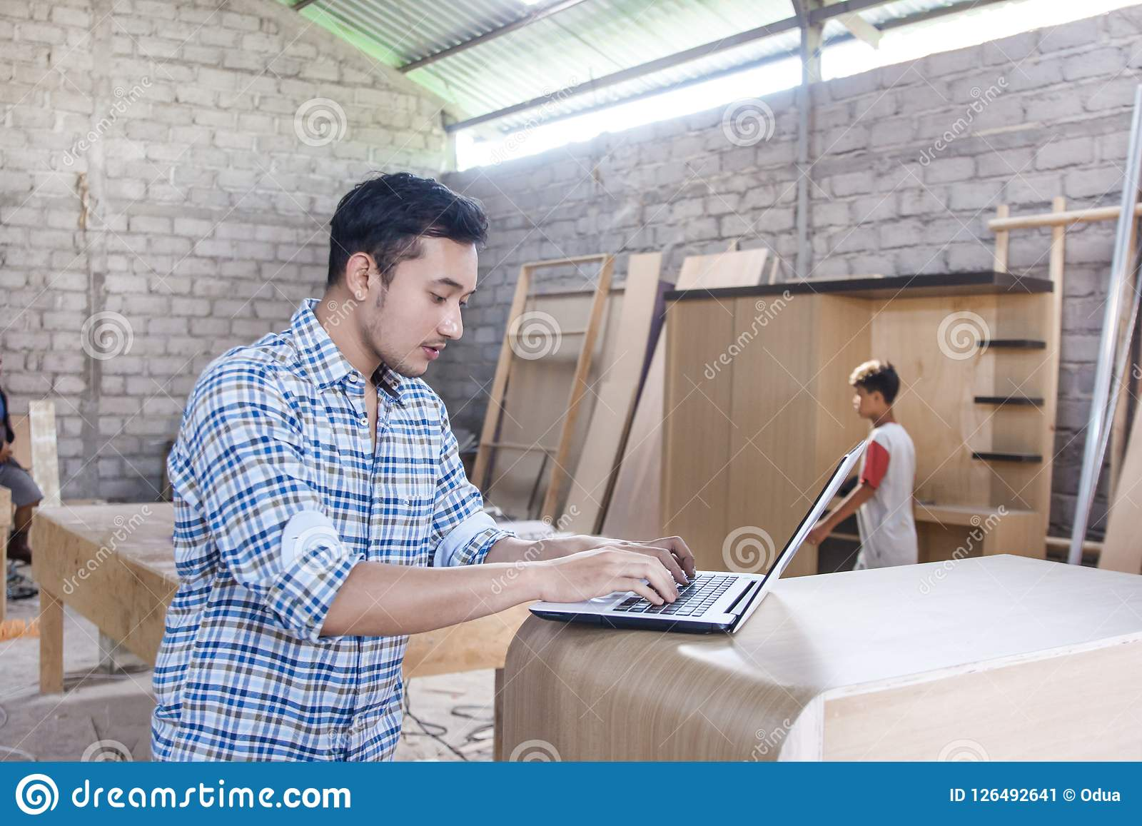 Carpintero joven que trabaja en su ordenador portátil