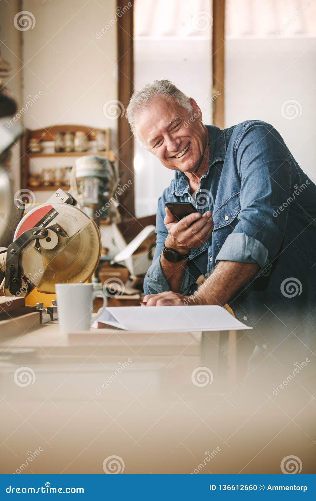 Carpintero mayor en su taller usando el teléfono móvil