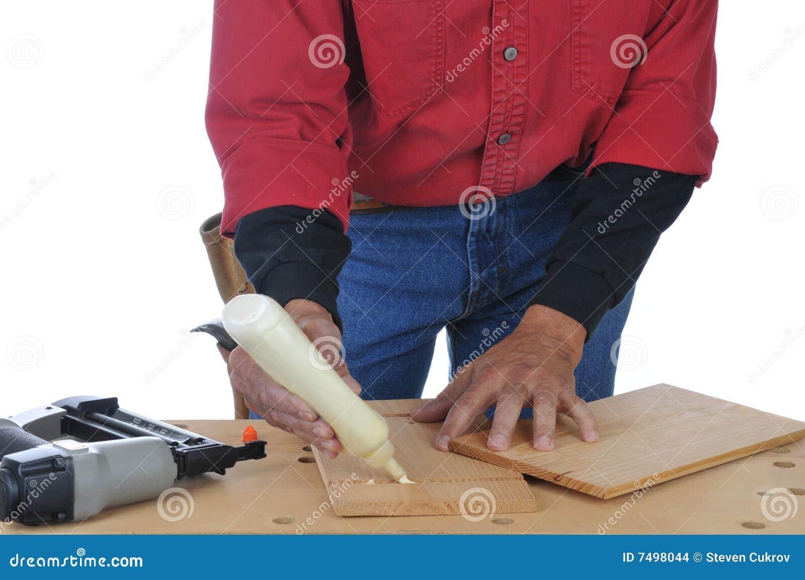 Carpintero que aplica el pegamento