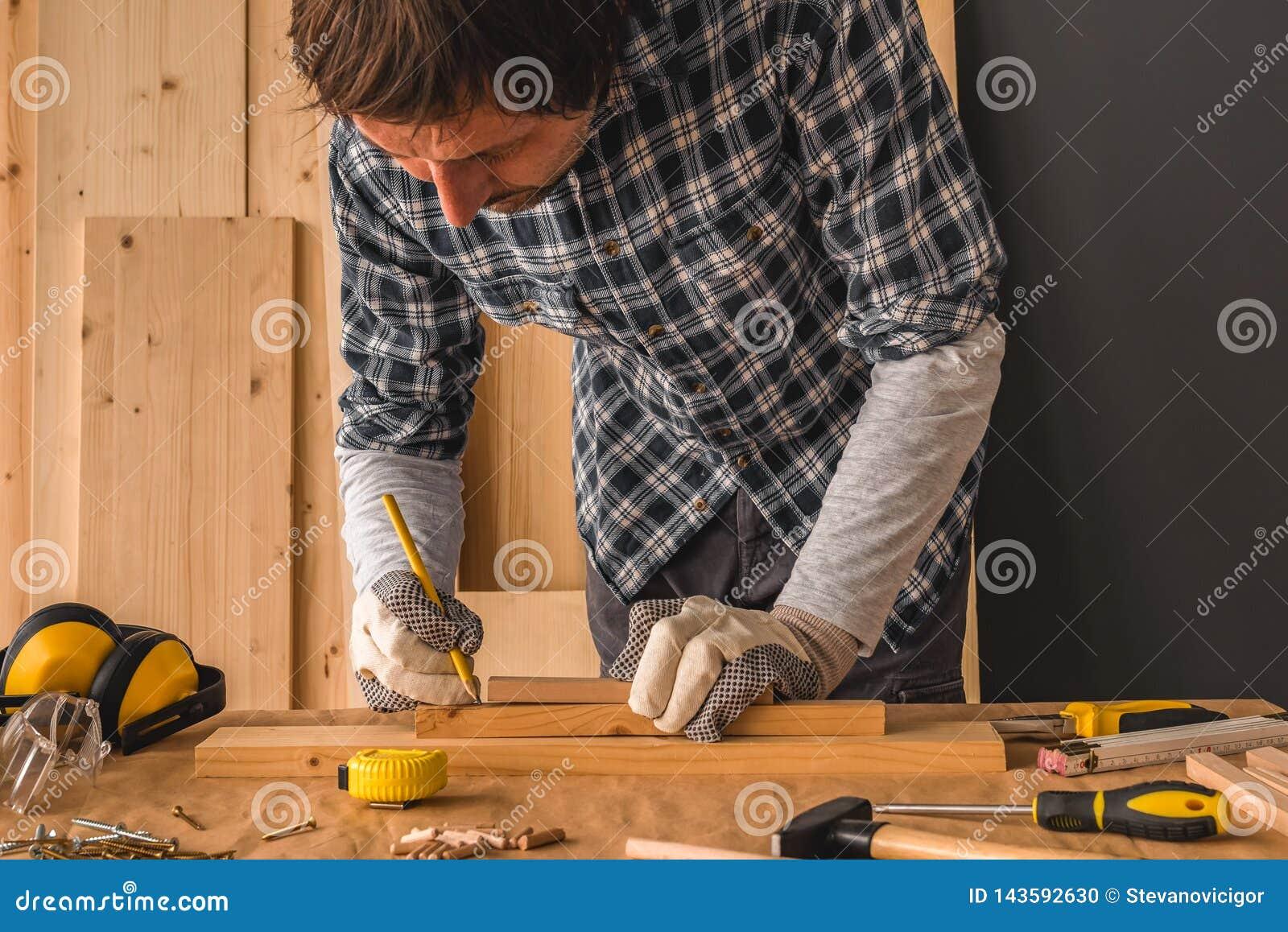 Carpintero que bosqueja el tablón de madera de pino para cortar en taller