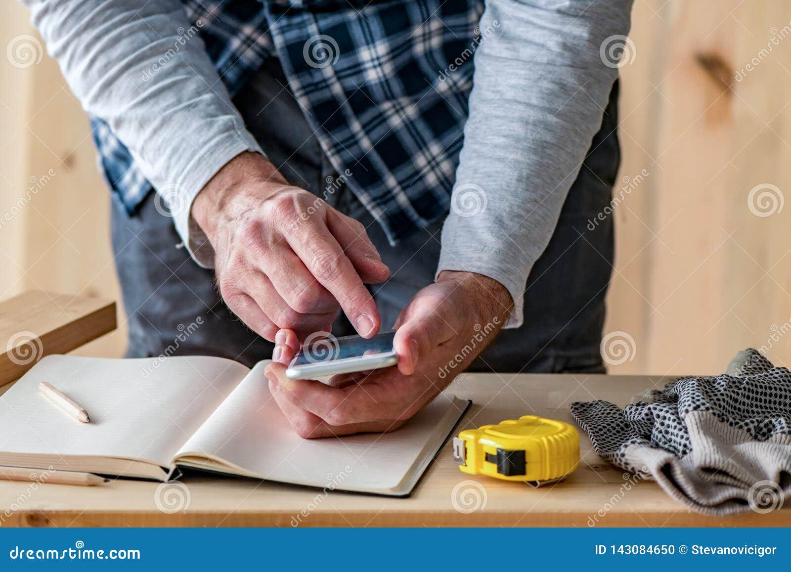 Carpintero que hace el cálculo del proyecto usando el app del smartphone