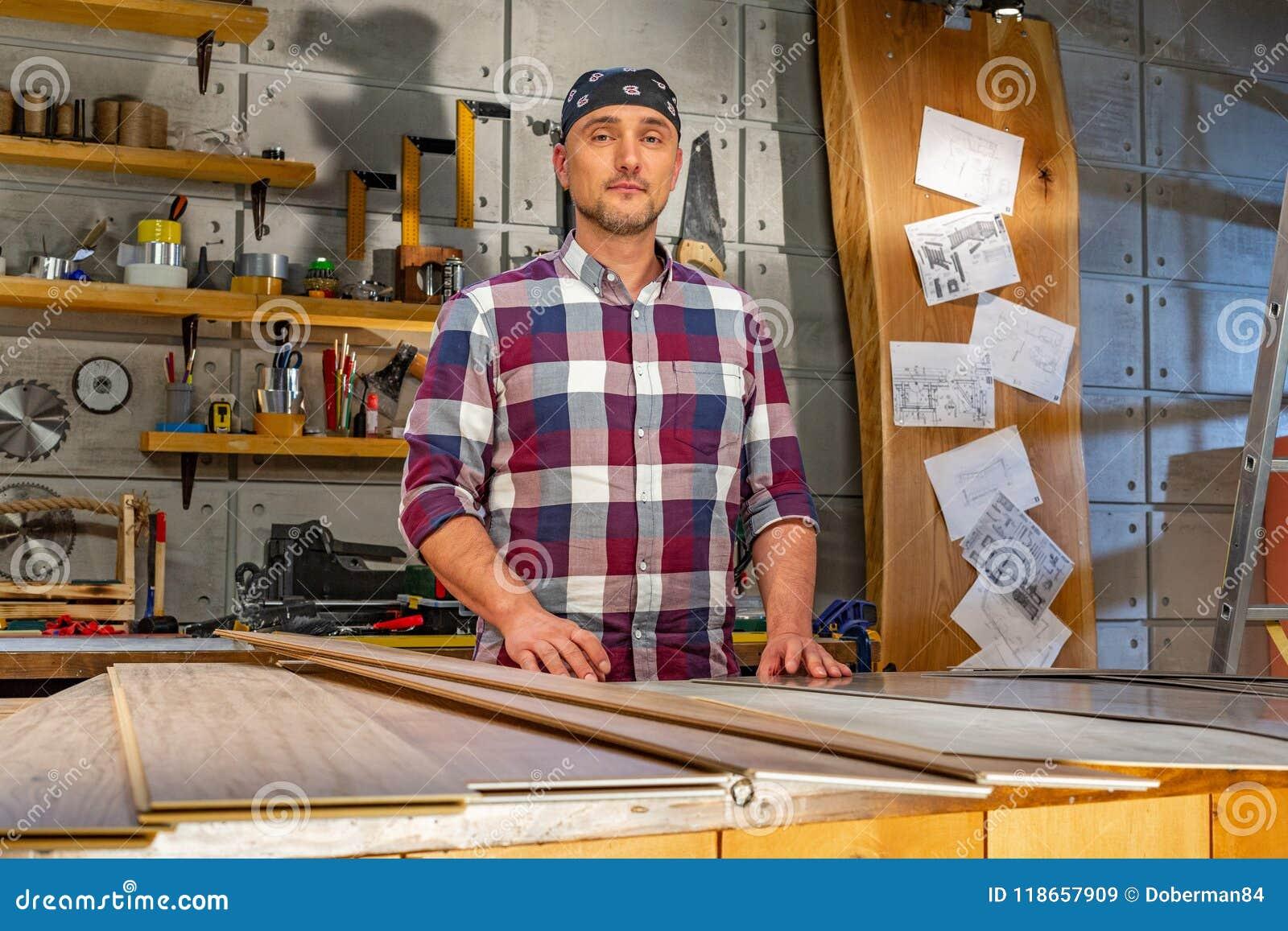 Carpintero que hace su trabajo en taller de la carpintería un hombre en un taller de la carpintería mide y lamina de los cortes