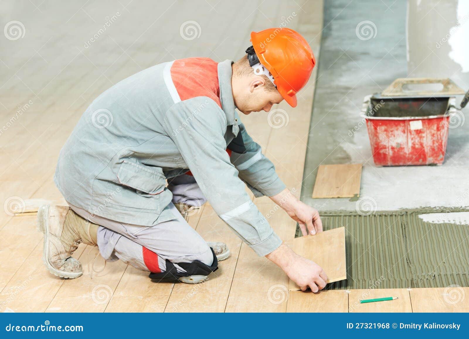 Carreleur au travail de rénovation industriel de carrelage d étage