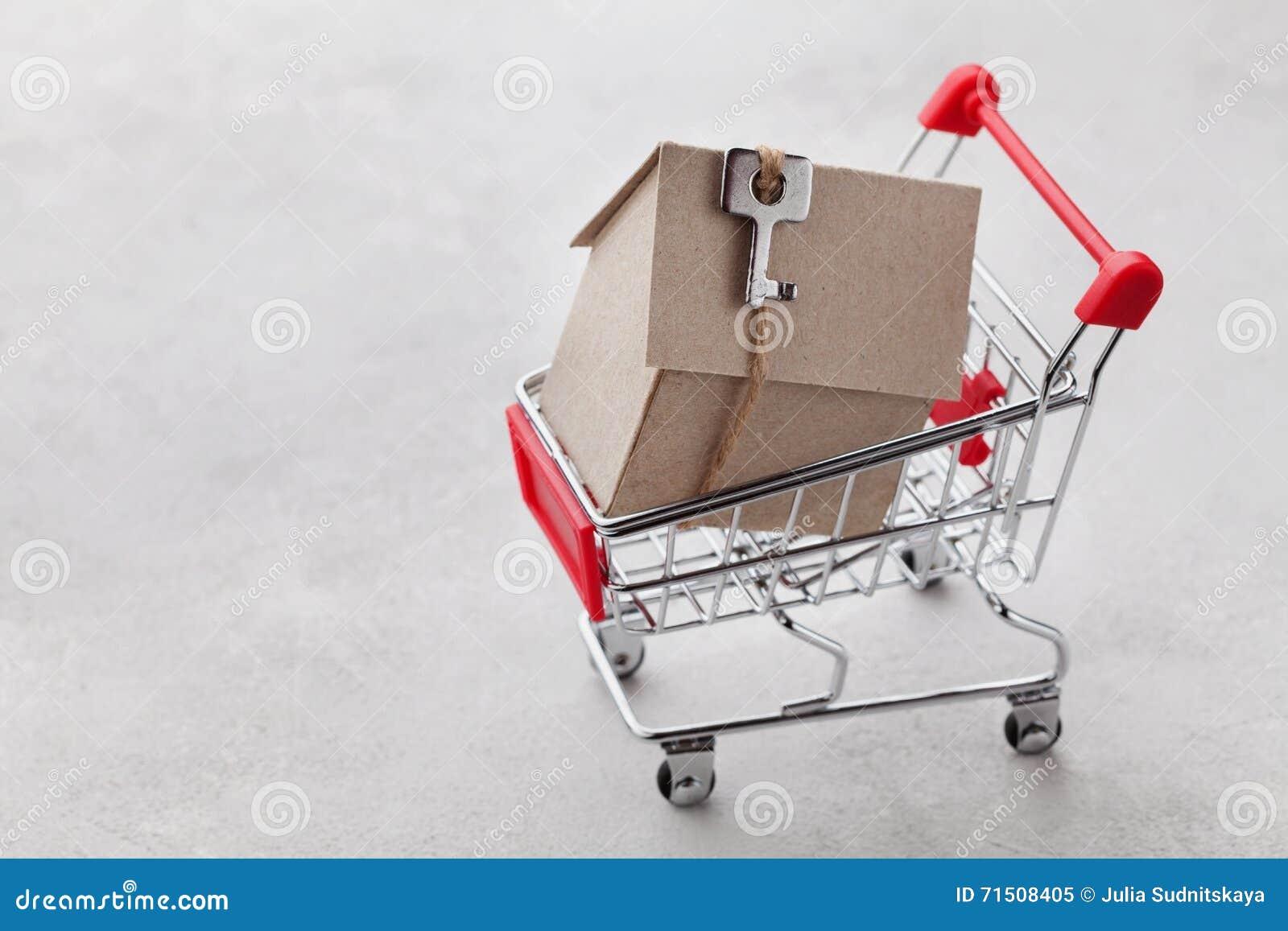 Carrello con il modello della casa del cartone su fondo grigio, comprando una nuova casa o vendita del concetto del bene immobile